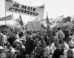 Civilians and soldiers stood beneath a banner during a demonstration in Seoul in April 1953 against resumption of the Korean peace talks. Associated Press